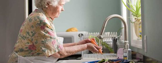 older woman washes carrot